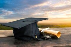 o tampão da graduação, chapéu com papel do grau na tabela de madeira vazia apronta-se imagens de stock