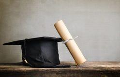 o tampão da graduação, chapéu com papel do grau na tabela de madeira vazia apronta-se foto de stock