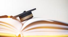 O tampão da graduação em livros pisa na sala da biblioteca do terreno e unive fotos de stock royalty free
