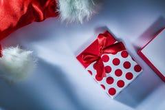 O tampão de Santa envolveu a caixa atual na superfície branca fotografia de stock royalty free
