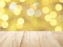 O tampo da mesa de madeira marrom vazio do close-up com ouro amarelo defocused e White Christmas ilumina o fundo do bokeh Fotos de Stock Royalty Free