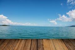 O tampo da mesa de madeira no fundo azul borrado do mar - pode ser usado para a exposição ou a montagem seus produtos Foto de Stock