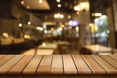 O tampo da mesa de madeira no fundo do café do bokeh do borrão pode ser usado para o dis fotografia de stock royalty free