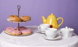 O tampo da mesa encheu-se com as xícaras de chá, um bule, o açúcar e os anéis de espuma Imagem de Stock Royalty Free
