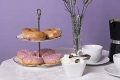 O tampo da mesa encheu-se com as xícaras de chá, um bule, o açúcar e os anéis de espuma Imagens de Stock Royalty Free