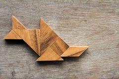 O tangram de madeira como peixes dá forma ao sawfish no fundo de madeira foto de stock royalty free
