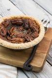 O tarte de pecan redondo pequeno caseiro do caramelo serviu com a forquilha do vintage no fundo de madeira imagens de stock royalty free