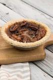 O tarte de pecan redondo pequeno caseiro do caramelo serviu com a forquilha do vintage no fundo de madeira fotos de stock royalty free
