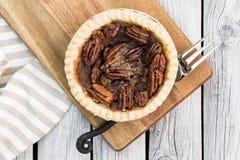 O tarte de pecan redondo pequeno caseiro do caramelo serviu com a forquilha do vintage no fundo de madeira Configuração lisa fotografia de stock
