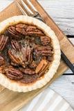 O tarte de pecan redondo pequeno caseiro do caramelo serviu com a forquilha do vintage no fundo de madeira Menu da sobremesa da a imagens de stock royalty free