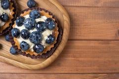 O tartlet em uma placa de madeira na tabela, uva-do-monte da uva-do-monte cozeu o escudo, queque do fruto com mirtilo fotos de stock