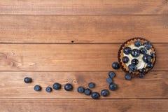 O tartlet em uma placa de madeira na tabela, uva-do-monte da uva-do-monte cozeu o escudo, queque do fruto com mirtilo imagens de stock