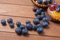 O tartlet em uma placa de madeira na tabela, uva-do-monte da uva-do-monte cozeu o escudo, queque do fruto com mirtilo imagem de stock