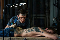 O Tattooist faz as caras Fotos de Stock