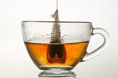 O Teabag em um copo encheu-se com água quente imagens de stock