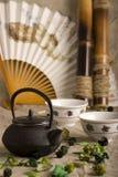 O teapot chinês, dois copos, ventilador e bambu Imagens de Stock Royalty Free