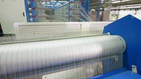 O tear da fábrica tece a fibra branca em uma sala da facilidade filme