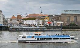 O teatro reconstruído famoso para peças por William Shakespeare no rio Tamisa, Londres com um cruzeiro do rio do olho de Londres imagens de stock royalty free