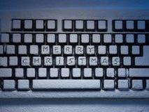 O teclado de computador com Feliz Natal do texto nos botões cobertos com a neve iluminou-se pela luz Fotografia de Stock