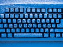 O teclado de computador com Feliz Natal do texto nos botões cobertos com a neve iluminou-se pela luz ciana Imagem de Stock Royalty Free