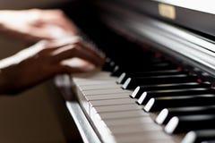 O teclado de piano brilhante clássico com jogador do pianista entrega o jogo de i foto de stock