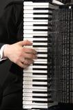 O teclado de um acordeão com uma mão fotografia de stock royalty free