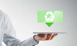 O tela táctil da mão do homem de negócios recicla ícones do sinal em uma tabuleta Fotografia de Stock