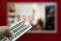 O telecontrole nos canais do interruptor da mão na tevê que pendura na parede vermelha Fotografia de Stock