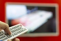 O telecontrole nos canais do interruptor da mão na tevê que pendura na parede vermelha Imagem de Stock