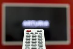 O telecontrole nos canais do interruptor da mão na tevê que pendura na parede vermelha imagens de stock