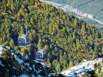 O teleférico desce de uma inclinação de montanha nevado em um vale verde com uma estância de esqui fotografia de stock