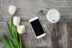 O telefone, o caf? e as flores brancos est?o na tabela Trabalho em casa freelance fotos de stock