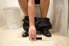 O telefone caiu e quebrou no toalete Fotos de Stock