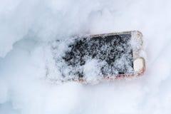 O telefone celular caiu acidentalmente para fora e obteve perdido na neve fotos de stock