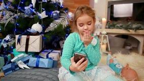 O telefone celular da foto, menina bonito que faz fotos do selfie, a criança usa o dispositivo para criar fotos e comunicar-se filme