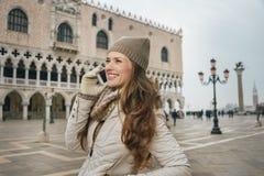O telefone celular de fala de sorriso do turista da mulher no St marca o quadrado Fotografia de Stock Royalty Free
