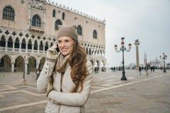 O telefone celular de fala do turista da mulher no St marca o quadrado, Veneza Foto de Stock