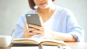 O telefone celular e a escrita do uso da mulher de negócios relatam na tabela de madeira Mulher asiática que usa o telefone e a x filme
