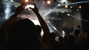 O telefone celular nas mãos da menina faz o vídeo na multidão da dança do fundo no concerto de rocha filme