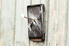 O telefone celular obsoleto é pregado a uma cerca de madeira foto de stock royalty free