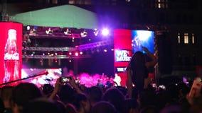 O telefone celular remove à disposição o concerto, muito pessoa em um festival de música, povos felizes, salto, dança na rocha video estoque