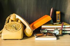 O telefone e os artigos de papelaria na mesa imagem de stock
