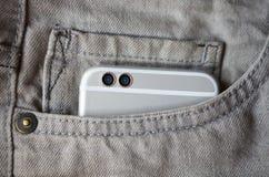 O telefone esperto da câmera dupla moderna nas calças de brim pocket Fotografia de Stock