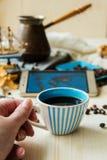 O telefone esperto da imprensa da mão com copo de café e fone de ouvido, conceito tudo pode fazer em sua mão pelo telefone espert Imagem de Stock Royalty Free