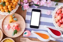 O telefone esperto da tela vazia com frutos de imitação deleitáveis, frutifica feijões de Mung dados forma, sobremesa tradicional imagens de stock royalty free