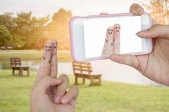 O telefone esperto do uso da mão toma a foto amantes engraçados do dedo imagem de stock royalty free