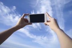 O telefone esperto do uso da mulher toma uma foto do céu azul e da nuvem bonita, monitor preto do isolado Imagem de Stock