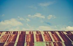 O telhado de aço oxidado e resistido velho da cabana do quonset contra um céu azul com fluff nubla-se o tom do vintage fotografia de stock