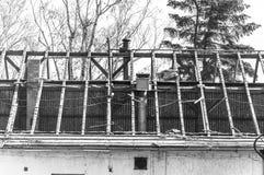 O telhado desmoronado da casa abandonada velha com feixes de madeira, danificada e destruída na zona de guerra ou no desastre dra Fotografia de Stock