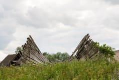 O telhado falhado de uma construção de madeira abandonada entre a grama verde alta, foco seletivo fotos de stock